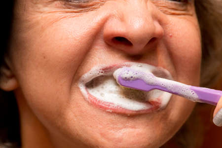 Woman Brushing her Teeth in Front of the Mirror