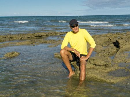 Man at a rocky beach wearing a yellow UV shirt enjoying himself sitting on the rocks Standard-Bild
