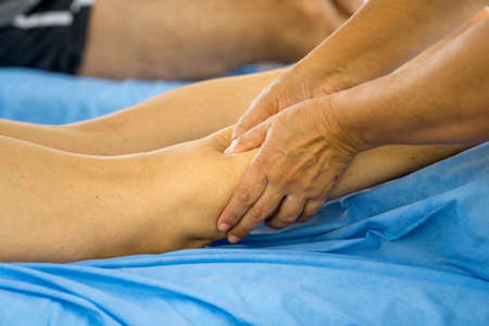 Massage Therapist Massaging a Women's Calf Muscle