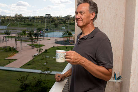 Senior Man Drinking a Cup Coffee Outside on his Balcony