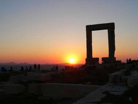 naxos: sun set behind the naxos arch in greece Stock Photo