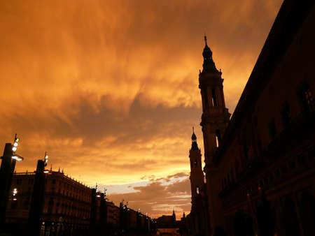 zaragoza: magnificant orange sky as the sun sets, showing the silhouette of basilica del pilar in zaragoza, spain Stock Photo