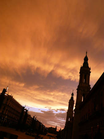 magnificant orange sky as the sun sets, showing the silhouette of basilica del pilar in zaragoza, spain photo