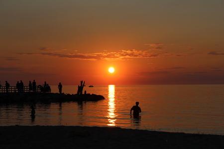 People enjoying sunset at Lake Michigan Stock Photo