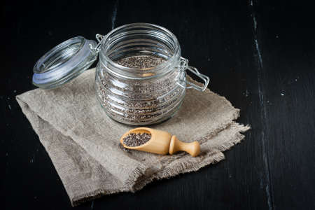 glass jar: Superfood Chia seeds in a glass jar with wooden spoon