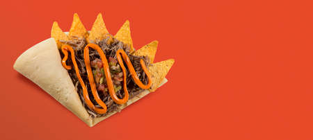 TOP VIEW OF CREPE OR FINE PANCAKE with nachos, meat and cheddar cheese IN orange BACKGROUND
