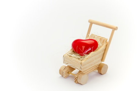 Heart in the baby carriage against a white background