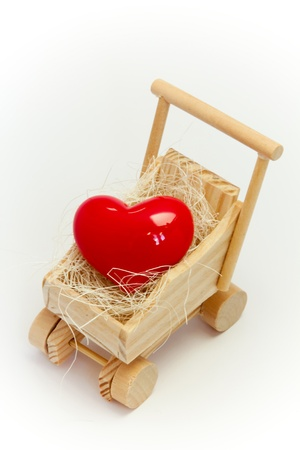 Heart in the baby carriage against a white background photo