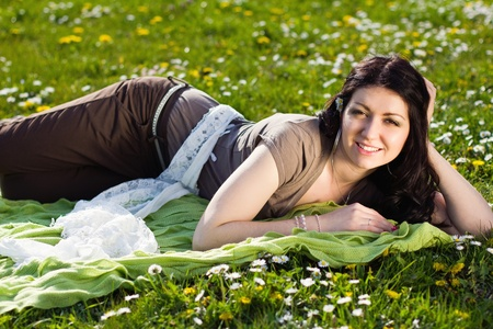 The image of a beautiful girl lying on the grass with flowers Stock Photo - 13534657
