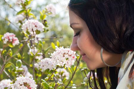 smells: A young woman smells the spring flowers Stock Photo