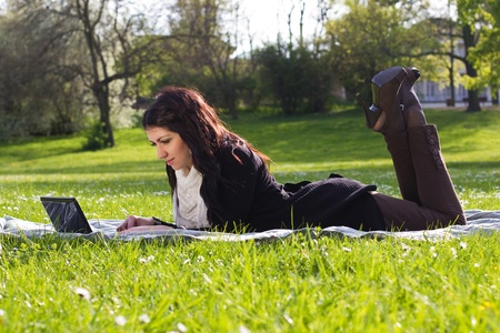 Young woman working with netbook outdoors in park on grass
