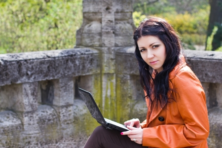 Young woman sitting on a bench and working on laptop photo