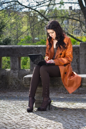 Young woman sitting on a bench and working on laptop Stock Photo