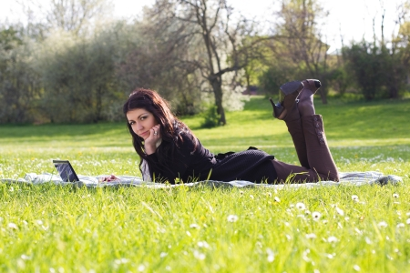 Young woman working with netbook outdoors in park on grass photo