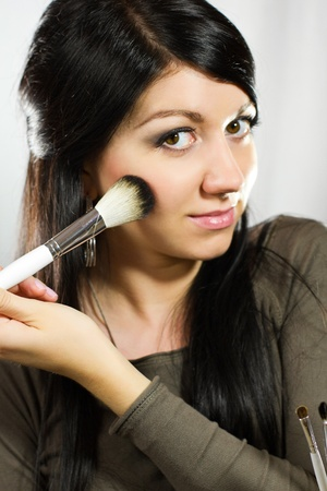 Portrait of beautiful young adult woman applying cosmetic photo