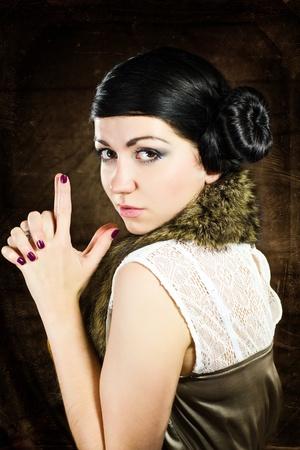 Retro portrait of brunette woman making a gun with hands photo
