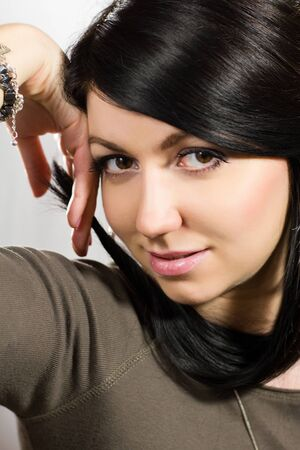 Close-up of young beautiful woman holding her hairs photo