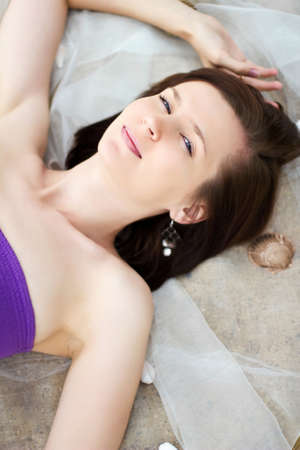 Beautiful girl is lying on fabric and sand with sea shells photo