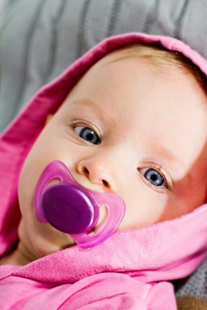 soother: Adorable infant with pink dummy