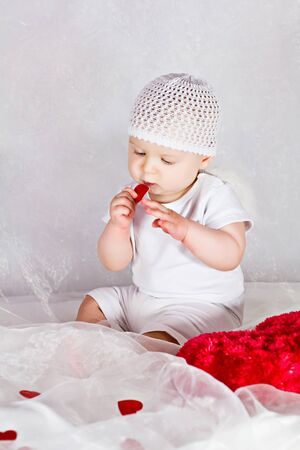 Angel baby is playing with red hearts Stock Photo - 15217216