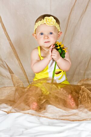 Pretty baby girl taking in her s arms the yellow flower Stock Photo - 14994994