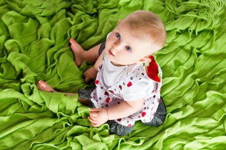 Baby sitting on green plaid and looking up. Birds-eye view