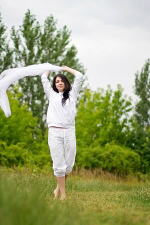 Outdoor portrait of beautiful girl with white light cloth photo