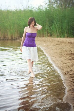 chillout: Pretty young girl walking on the river shore