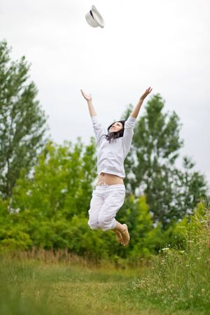 Beautiful woman throw her hat and jump photo