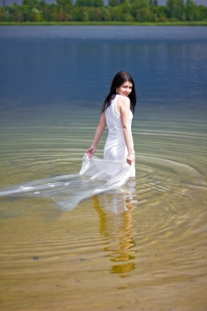undine: A young woman in white dress enjoys the waters of the lake Stock Photo