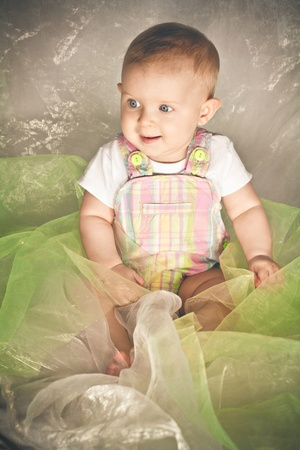 Smiling baby sitting enveloped in colored fabric. Soft colors Stock Photo