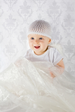 Cute smiling baby playing with white fabric photo