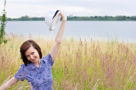Slim shaped girl enjoying nature in the meadow by the lake Stock Photo