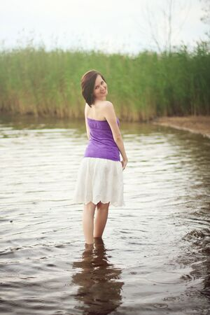 Young woman wading out of fresh water lake photo