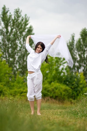 Young happy woman standing on the grass and holding a white piece of cloth in the wind photo