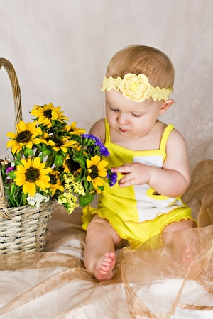 Baby looking and touching the flowers photo