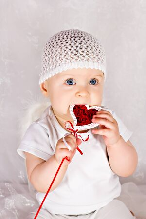 Cute baby girl is biting heart Stock Photo - 15304634
