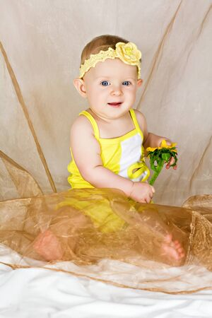 Beautiful little girl smiles and sits with yellow flower Stock Photo - 15391270