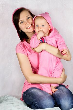 Happy mother and daughter in pink clothing