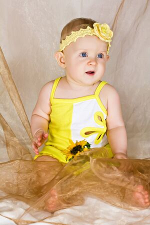 Little baby girl in yellow clothing and frontlet