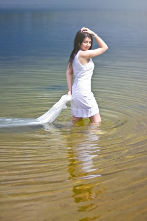 sea nymph: Sexy girl in white dress posing in the water of the lake