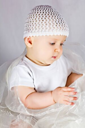 Little cute baby girl is playing with white fabric photo
