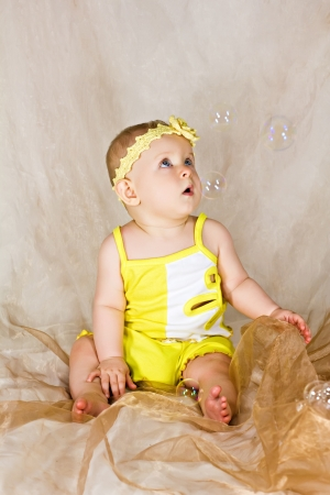 Adorable infant is looking to the soap bubbles photo