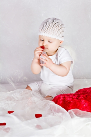 Little baby girl is playing with the hearts photo