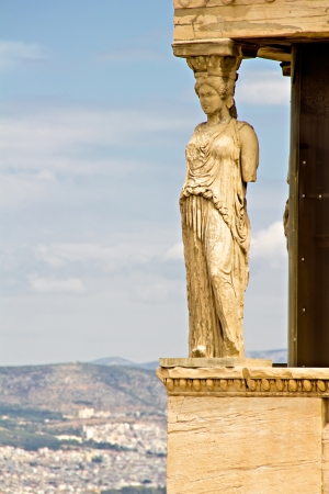 Greece, Athens, Acropolis, Caryatids Statue with Athens city in the background photo