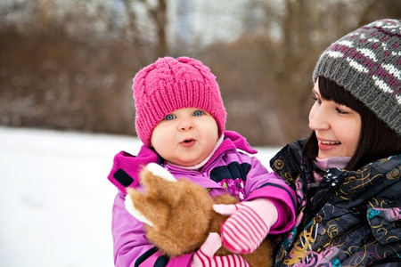 Happy little girl in winter with her mother photo