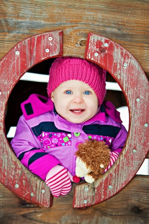 Little happy girl on playground with her toy hedgehog in winter photo
