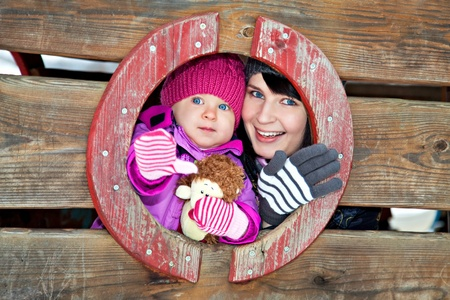 Happy mother and her daughter on winter playground photo