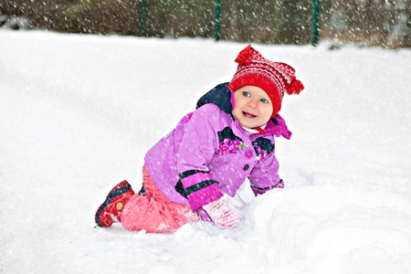 Cute adorable baby crawling in snow in winter park photo