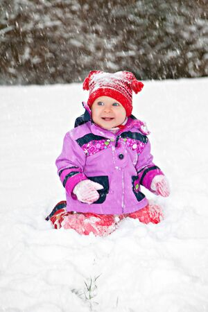 Cute adorable baby sitting on snow in winter park photo